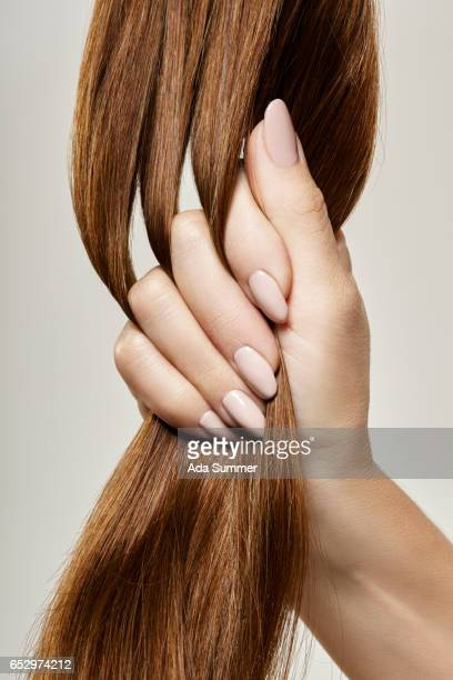 human female hand holding brown hair against gray background, close up - capelli o peli foto e immagini stock