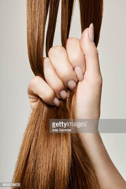 Human female hand holding brown hair against gray background, close up