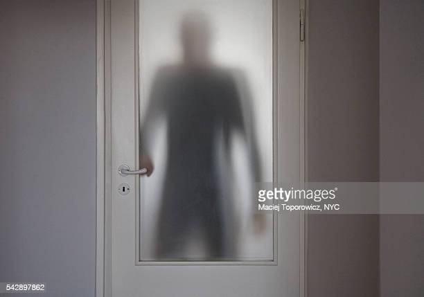 human figure entering room behind translucent doors. - stranger stock pictures, royalty-free photos & images