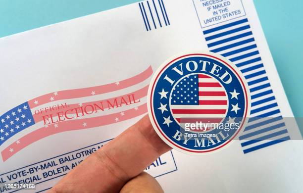 human finger holding sticker above voting mail - voting by mail stock pictures, royalty-free photos & images