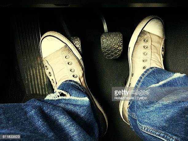 Human foot with brake and gas pedals in car