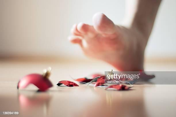 Human foot with broken Christmas tree ball