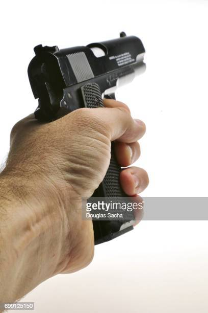 Human hand aims the pistol on a white background
