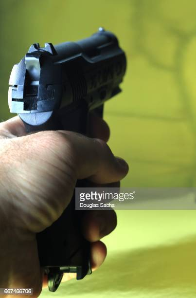 Human hand aims the pistol