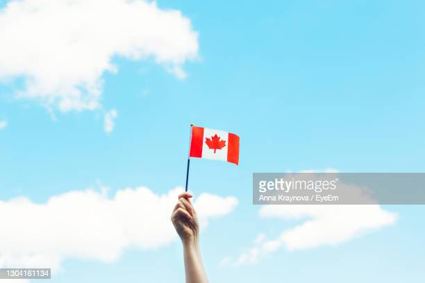 human hand arm waving canadian flag against blue sky.  national canada day on 1st of july outdoor. - canada day stock pictures, royalty-free photos & images