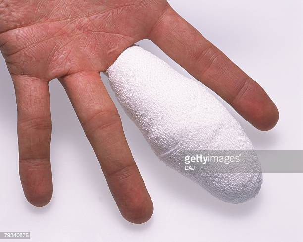 human hand bandaged middle finger - cut on finger stock photos and pictures