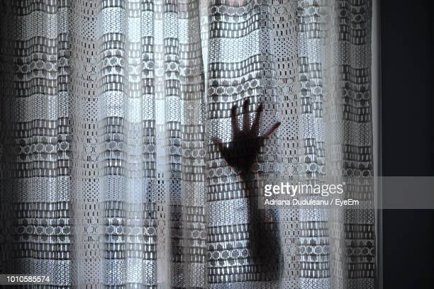 Human Hand Behind Window Curtain At Home