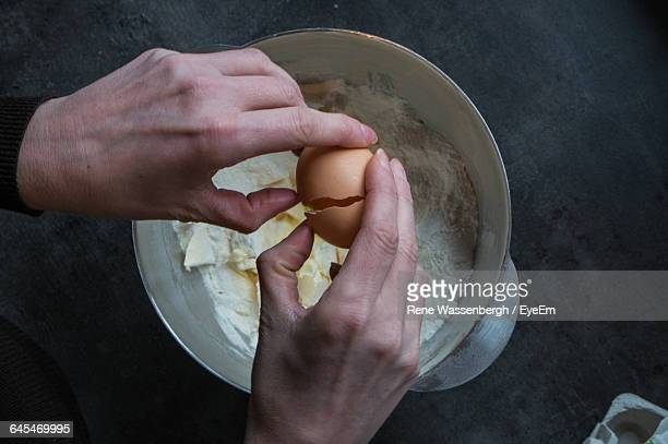 human hand breaking egg over mixing bowl - human egg stock photos and pictures