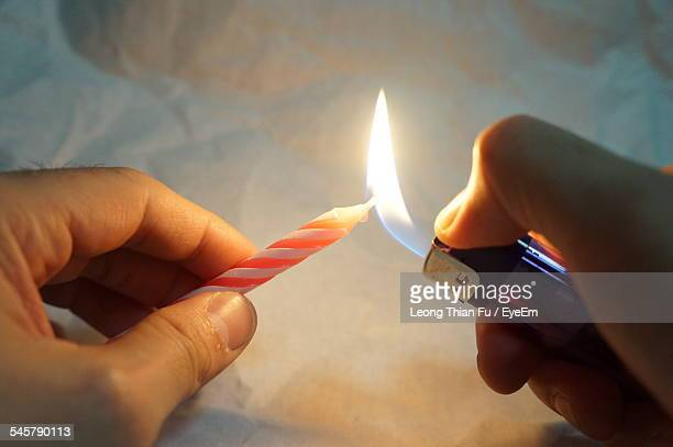 Human Hand Burning A Candle With A Lighter
