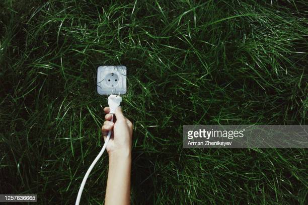 human hand connecting electrical plug to the outlet in green grass - plugging in stock pictures, royalty-free photos & images