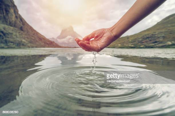 human hand cupped to catch fresh water from mountain lake, matterhorn switzerland - pinnacle peak stock pictures, royalty-free photos & images