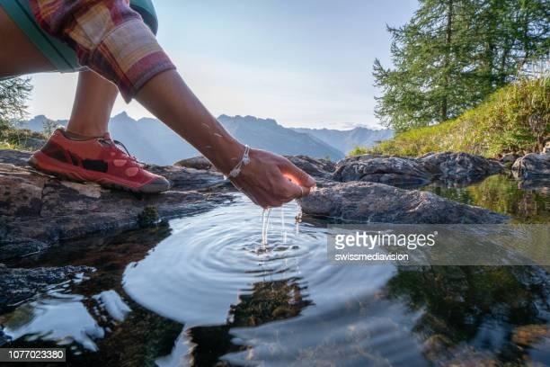 main de l'homme incurvé pour attraper l'eau douce du lac de montagne, suisse - pureté photos et images de collection