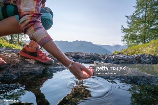 mão humana em concha para pegar água doce do lago de montanha, suíça - fonte - fotografias e filmes do acervo