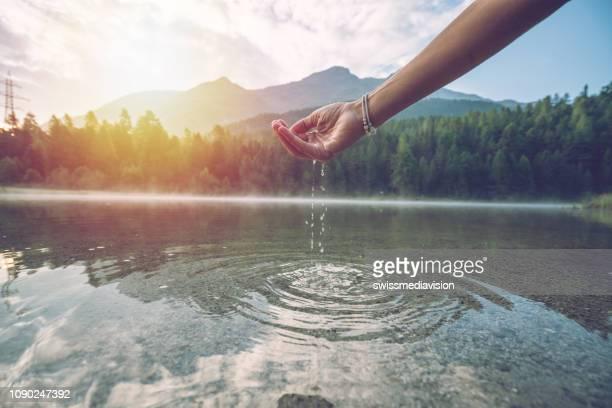 人間の手丸めは、マウンテン湖、スイスからの淡水をキャッチします - 湧水 ストックフォトと画像