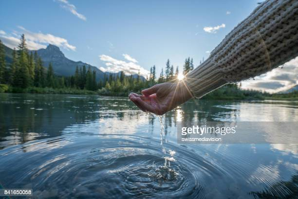Human hand cupped to catch fresh water from mountain river