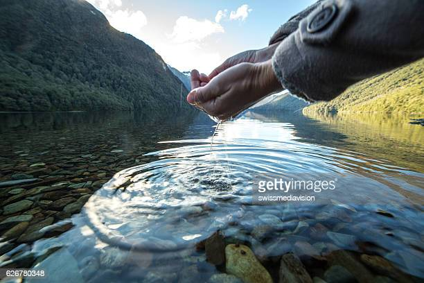Human hand cupped to catch fresh water from the lake