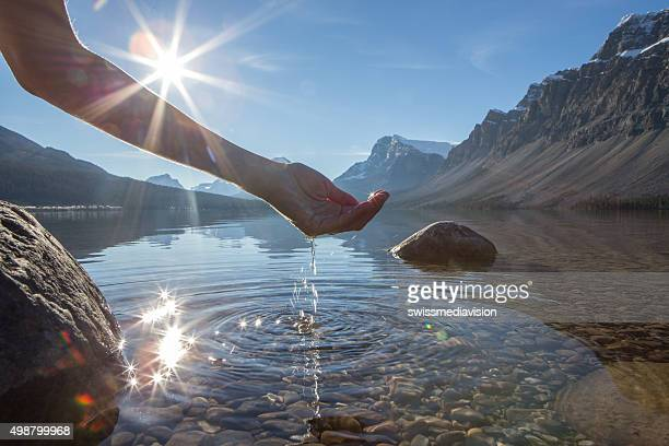 human hand cupped to catch the fresh water from lake - water stockfoto's en -beelden