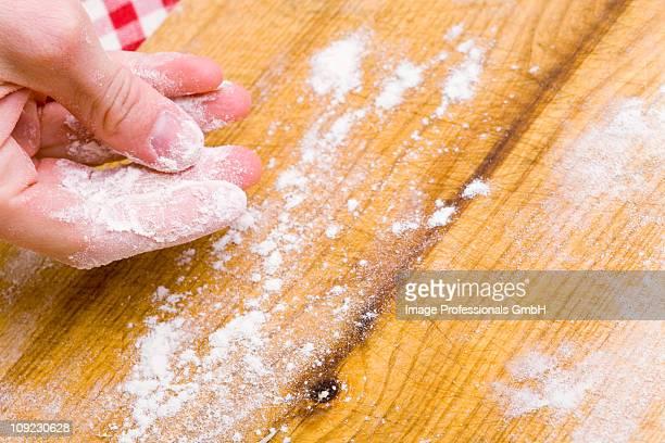 Human hand dusting flour on chopping board