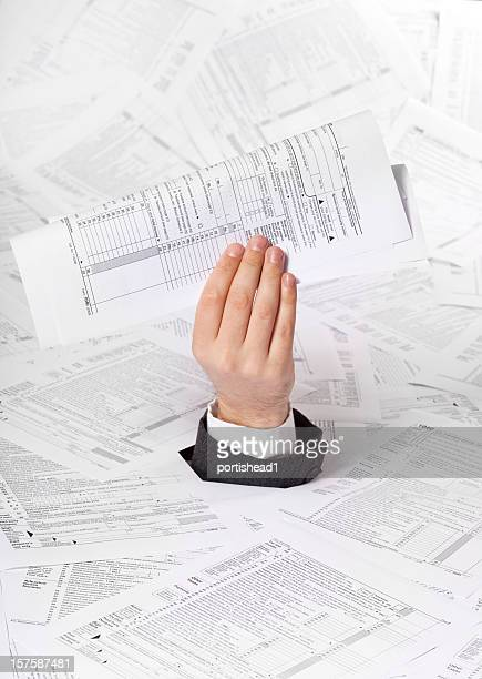 human hand emerging from paper sheets - 1040 tax form stock photos and pictures