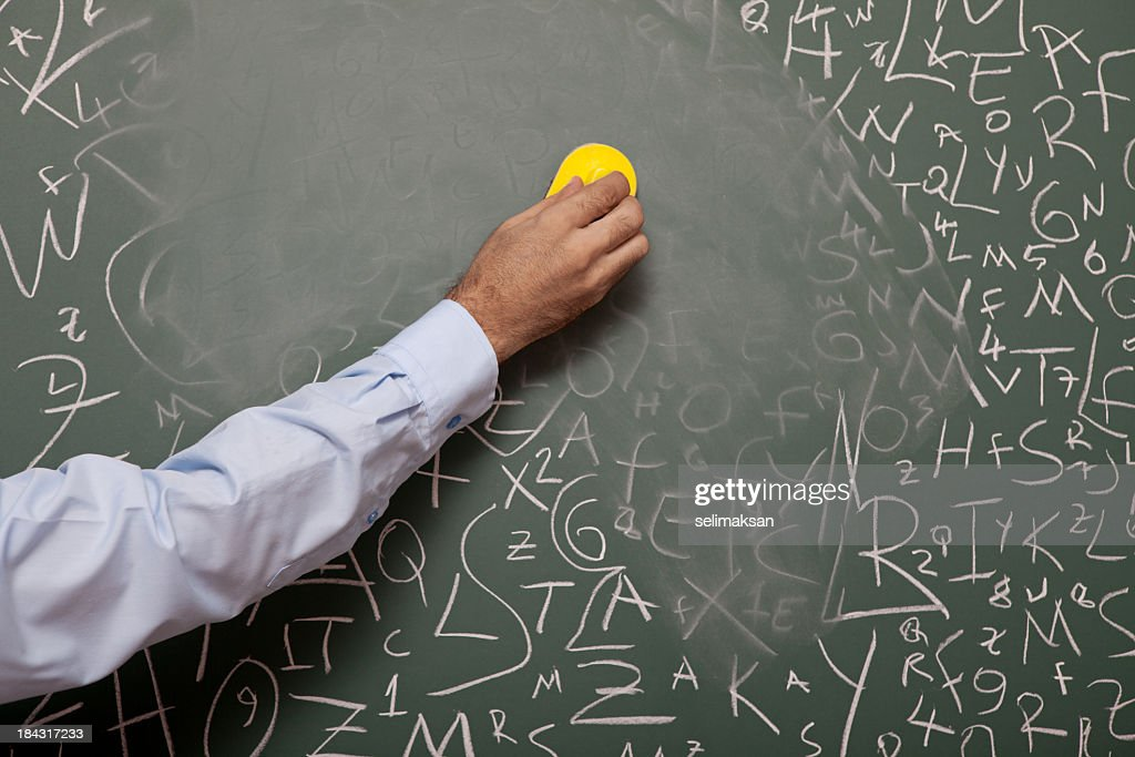 Human hand erasing blackboard with large amount of letters : Stock Photo