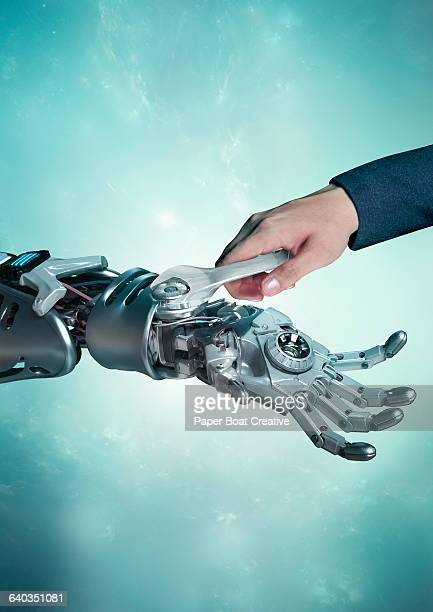 Human hand fixing a robot hand with a wrench