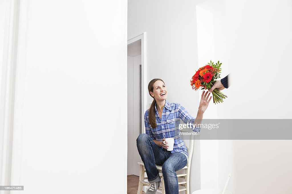 Human hand giving bunch of flowers to woman, smiling : Stock-Foto