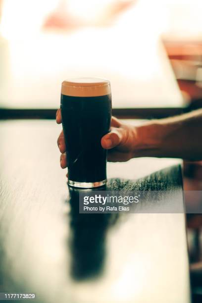 human hand grabbing pint of stout - irish culture stock pictures, royalty-free photos & images