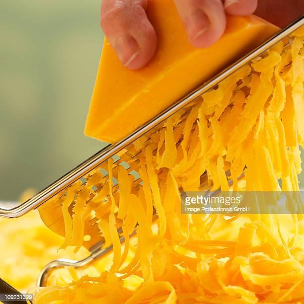 Human hand grating cheese, close-up