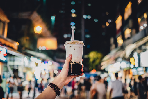 Human hand holding a bottle of iced cold bubble tea against busy city street at night - gettyimageskorea