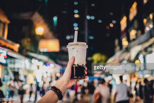 human hand holding a bottle of iced cold bubble tea against busy city street at night - taiwan fotografías e imágenes de stock