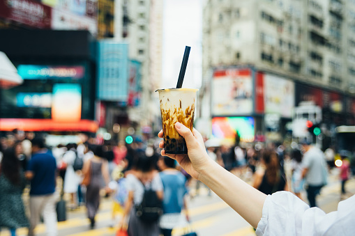 Human hand holding a bottle of iced cold bubble tea against busy downtown city street in a hot summer day - gettyimageskorea