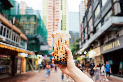 Human hand holding a bottle of iced cold bubble tea against city street in a hot summer day - gettyimageskorea