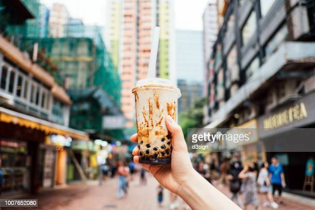 human hand holding a bottle of iced cold bubble tea against city street in a hot summer day - taiwan stock photos and pictures