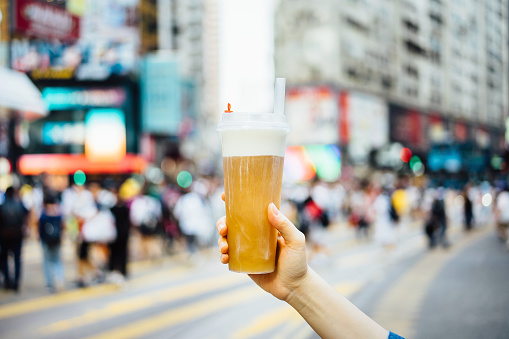 Human hand holding a bottle of iced cold tea drink against busy downtown city street in a hot summer day - gettyimageskorea
