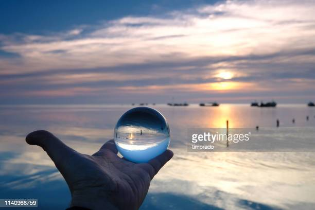 human hand holding a crystal ball by sevre niortaise river, deux-sevres, france - deux sevres fotografías e imágenes de stock