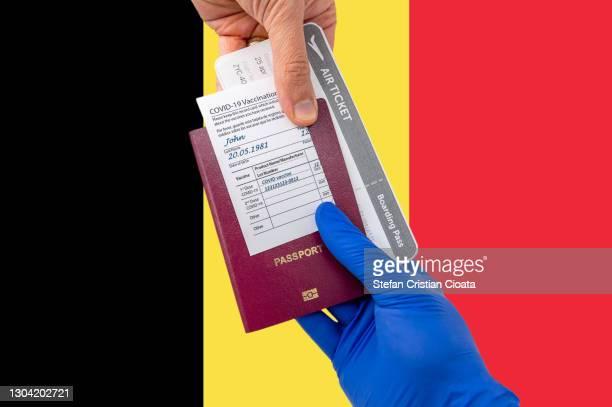 human hand holding a passport and vaccination certificate - belgische cultuur stockfoto's en -beelden