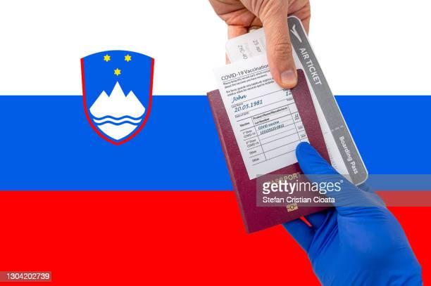 human hand holding a passport and vaccination certificate - スロベニア国旗 ストックフォトと画像
