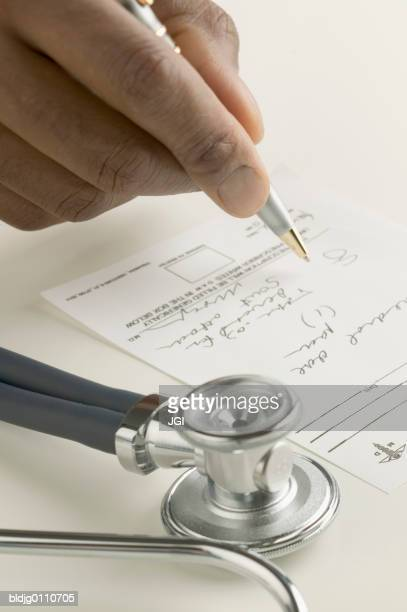 Human hand holding a pen signing a cheque