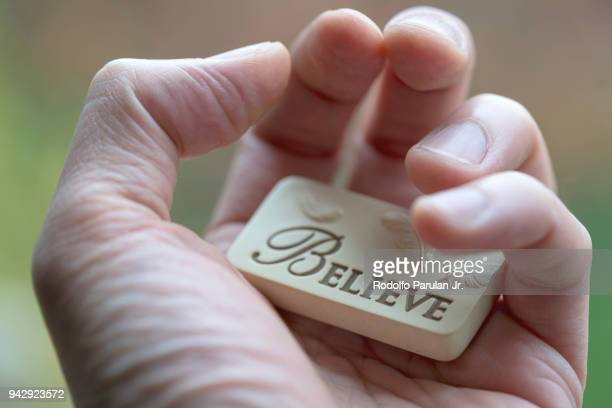 human hand holding a small resin cast block with the word believe engraved on it - resin drive stock pictures, royalty-free photos & images