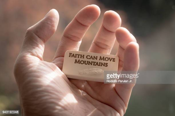 human hand holding a small resin cast block with words 'faith can move mountains' engraved on it - resin drive stock pictures, royalty-free photos & images