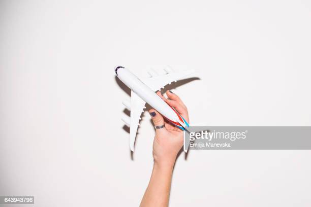 Human hand holding a toy plane