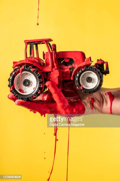 Human hand holding a toy tractor being splashed with red paint, taken on March 9, 2020.