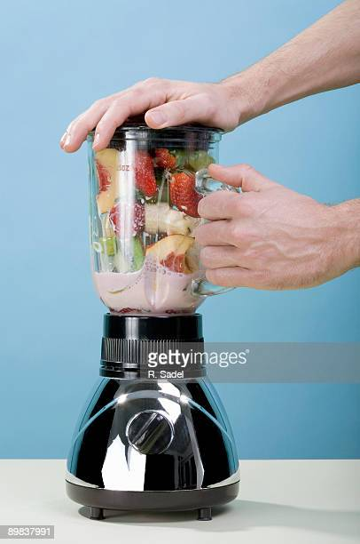 A human hand holding blender while it blends fruit