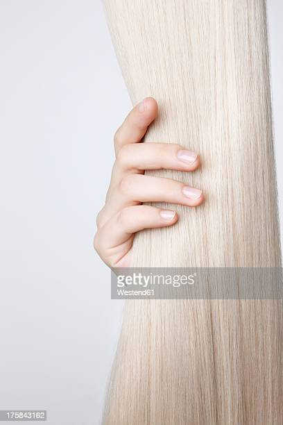 Human hand holding blond hair against white background, close up