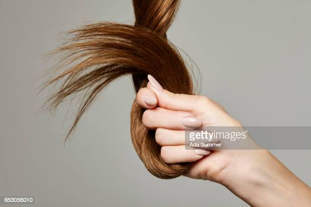 human hand holding brown hair against gray background, close up - cheveux ou poils photos et images de collection