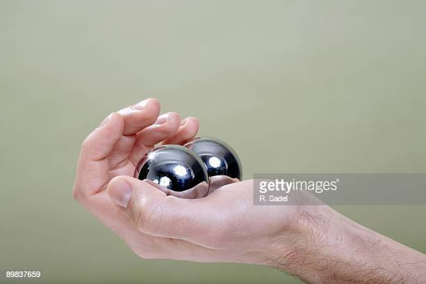 A human hand holding Chinese medicine balls
