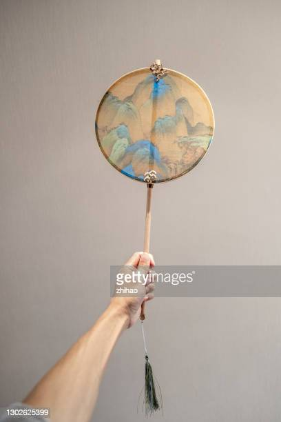 human hand holding chinese traditional round fan - chinese culture stock pictures, royalty-free photos & images