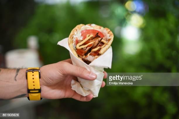 Human hand holding deletions gyro pita