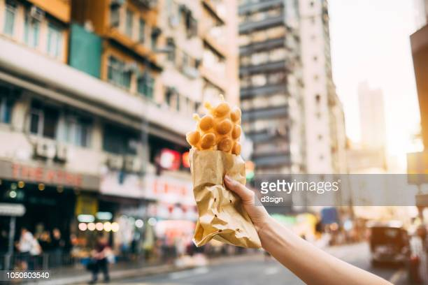 human hand holding freshly made traditional street snack egg waffle against city street in hong kong - fashion hong kong stock photos and pictures