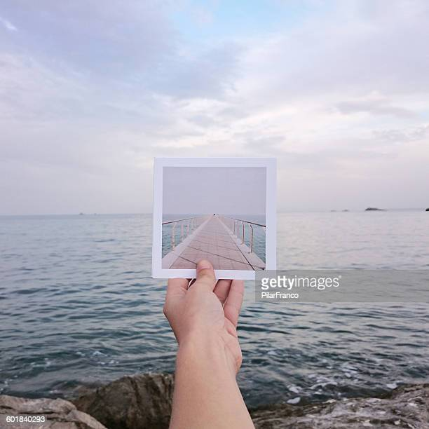 Human hand holding instant print transfer photo in front of the sea